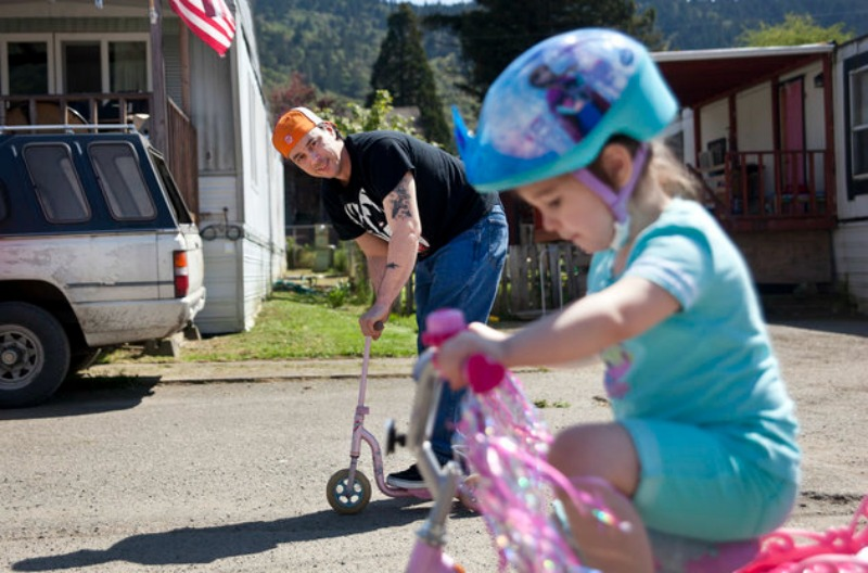 ·üýÀQ uc÷__·ìeüïª[Kåù=Ëù·ÿÙBryan Thouvenel rides on a scooter while watching his daughter Harmony, 5, on her bike in front of their house in Myrtle Creek, Saturday April 3, 2016. Thouvenel and Harmony were recently reunited a